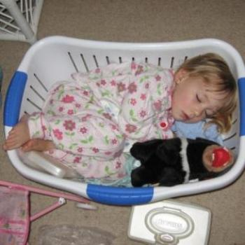 Laura asleep in the clothes basket